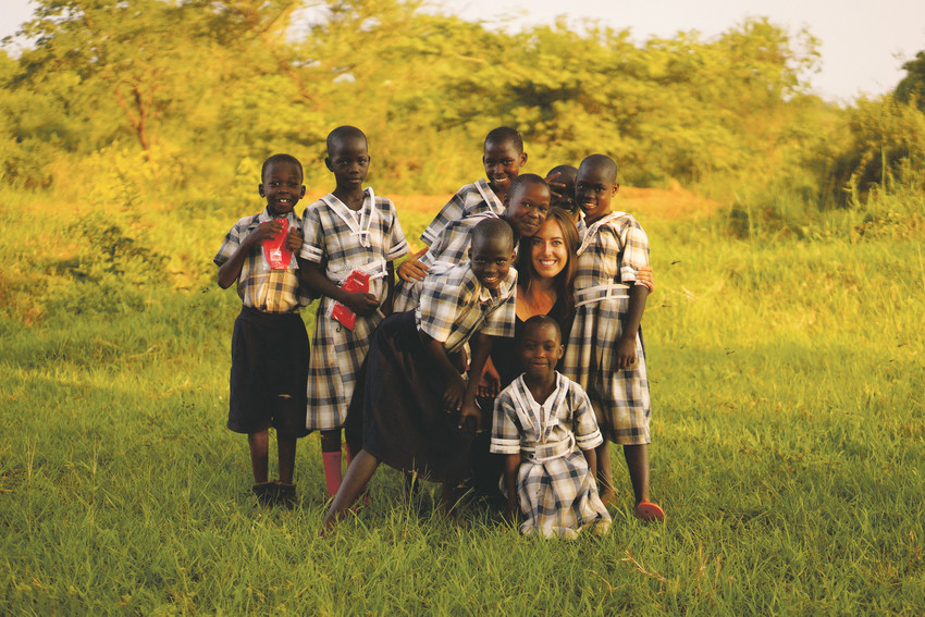 Jayme Ward, executive director and co-founder of Far Away Friends, poses with some Ugandan youths. She formed the nonprofit with Collines Angwech, to provide much needed educational opportunities to students in rural Uganda.