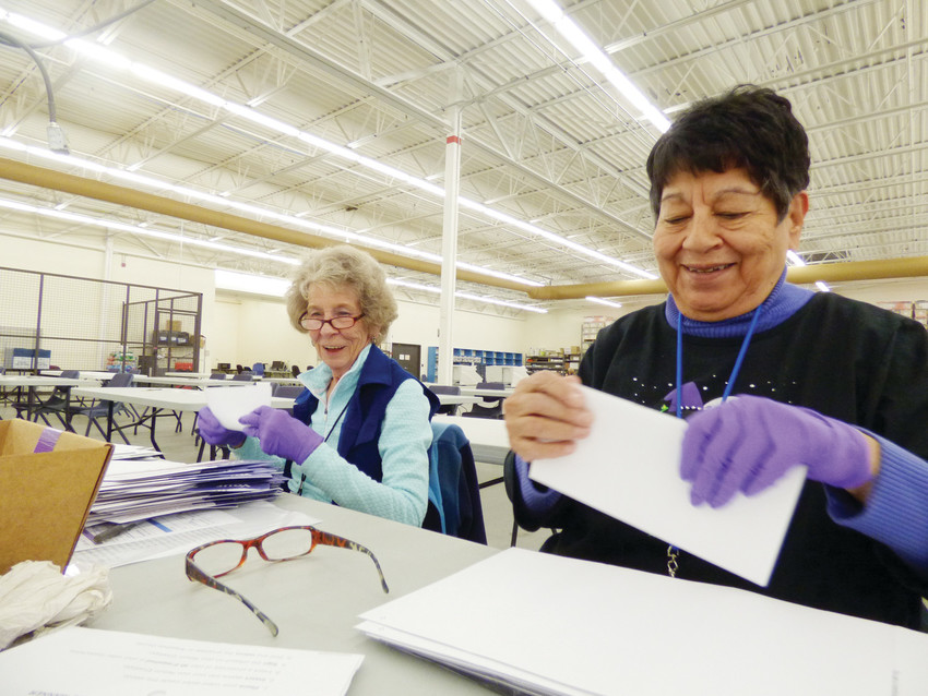 "Marilyn Fenner, left, and Martha Castillo-Garcia open mail-in ballots, examining each one for tears, smears, or stains. ""I've done this for years,"" Fenner said. ""It's fun to be part of the democratic process, and I get to see all my old friends."""