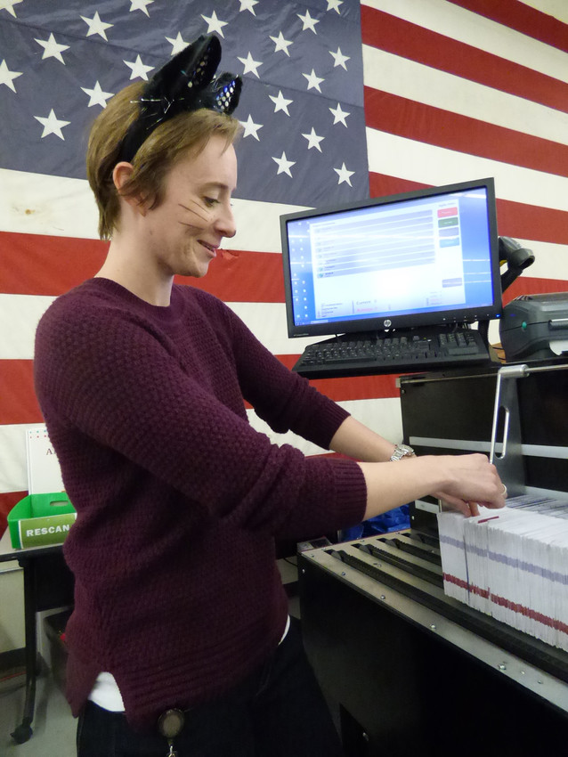Senior Ballot Receiving Specialist Marissa Chamberlain arranges recently arrived ballots into a sorting machine, which examines each ballot for weight, signature, barcode, and other attributes. Ballots that don't pass will go to a team of trained judges for examination.