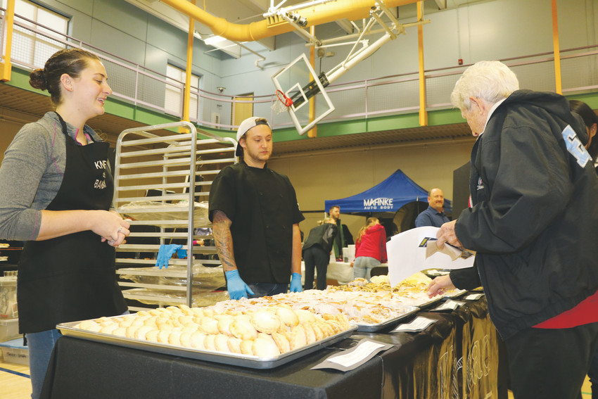 Bakers from The Knead Bakery offers mini apple pies and other baked goods for tasting during the annual Taste of Arvada on Oct. 26. The event gathered not only dozens of local restaurants, breweries and bars, but also local businesses together in the Apex Center.