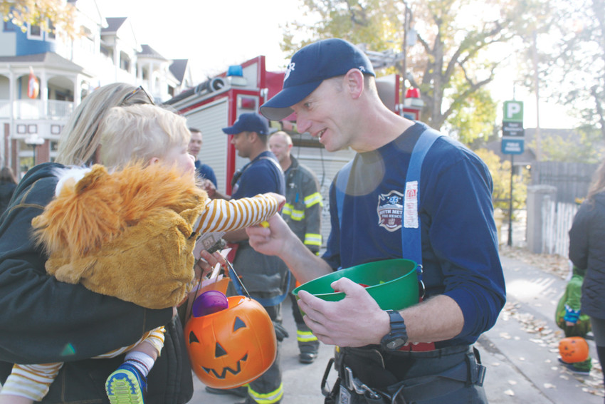 South Metro Firefighter Justin Lewis gives a tiger babe-in-arms a morsel of candy at the 2017 TOTOM.