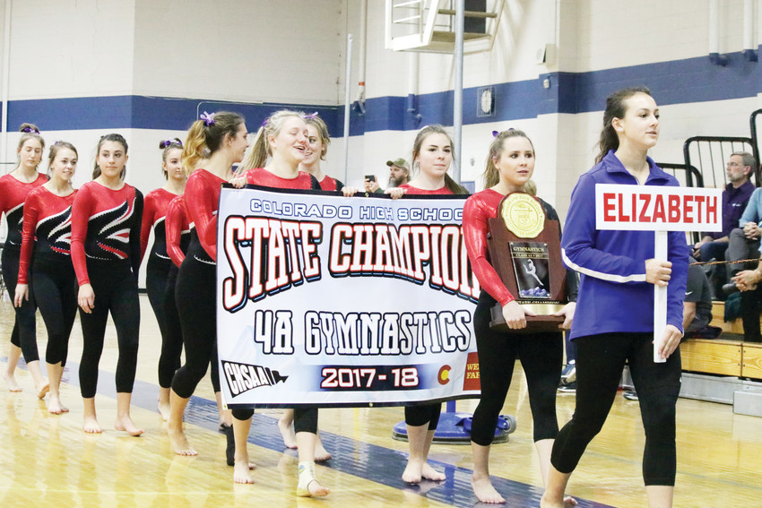 Anastasia Buzalsky carries the state trophy and teammates carry the state Class 4A gymnastics team championship banner as they march in to the Thornton High School gymnasium during the opening ceremonies of the Nov. 4 individual event championships. The Cardinals won the team trophy at the Nov. 3 Class 4A state gymnastics meet. Buzosky also won the state all-around championship at the meet.