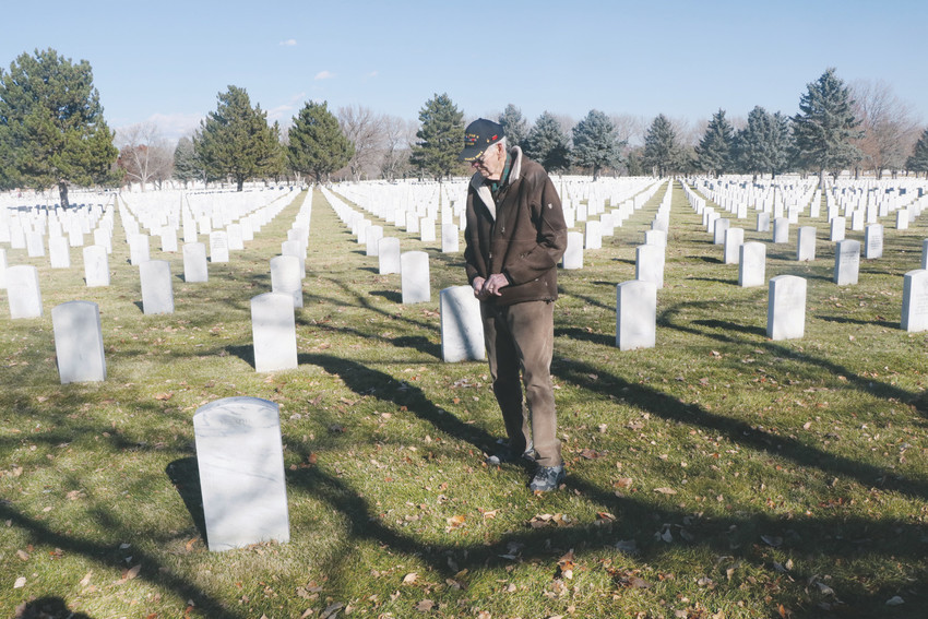Walter Ohmart, who served in the Navy in World War II, visits the resting place of family and friends before attending the Veterans Day ceremonies held Nov. 11 at Fort Logan National Cemetery. He said he always tried to visit to the graves of friend, comrades and family on Veterans Day to honor them for their service.