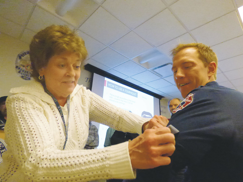 "Kathy Houston, left, cranks down a tourniquet on paramedic firefighter Ryan Rockx. Houston, who used to manage the blood bank at Children's Hospital, said the tourniquet technique was old hat to her. ""I think a lot more people need to know how to do this, and to take the Citizens' Academy,"" Houston said."