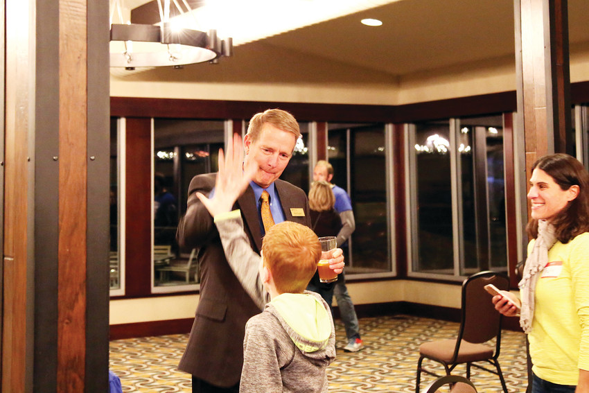 Jefferson County Public Schools Board of Education incumbent Brad Rupert gives a high five as his leading number come in during election night at the Applewood Golf Course.