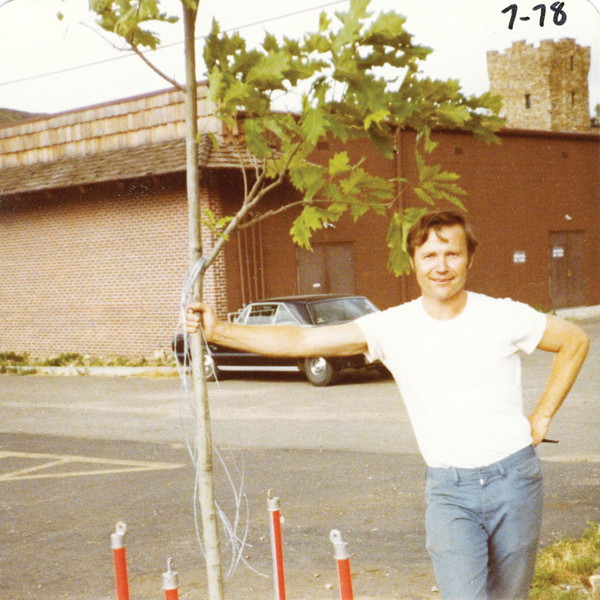 Conrad Gardner stands beside a tree he planted near the 1200 block of Arapahoe Street, circa 1978. The tree is still there today and has a small picnic area accompanying it.