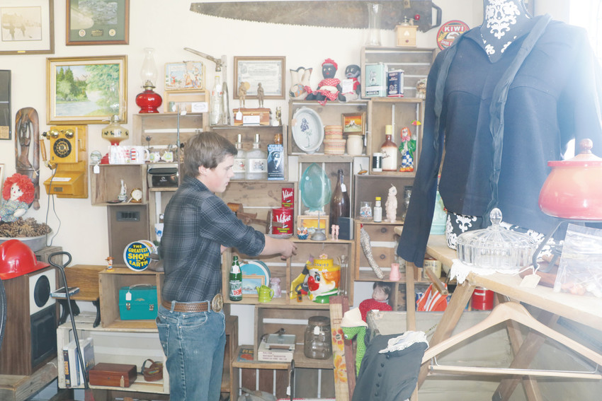 Garret Strain, son of owner Shawn Strain, talks about some of the items on sale at Barnwood Vintage at 166 Main St. in Elizabeth. The shop carries antiques but features vintage and rustic items the Strains have collected over the years.