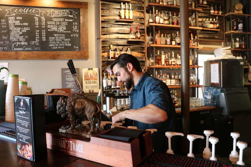 Kyle Gammage, coffee manager at The Bluegrass Coffee and Bourbon Lounge in Olde Town Arvada, makes a drink for a customer at the popular coffee bar.