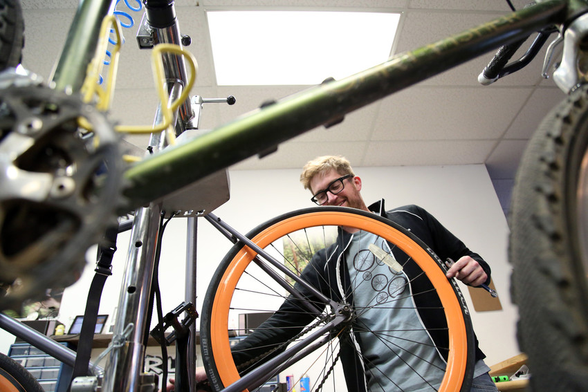 Nate Glore repairs a flat tire. Glore opened his bike shop, Cycle Dynamics, in Arvada a year and a half ago with a focus on service.