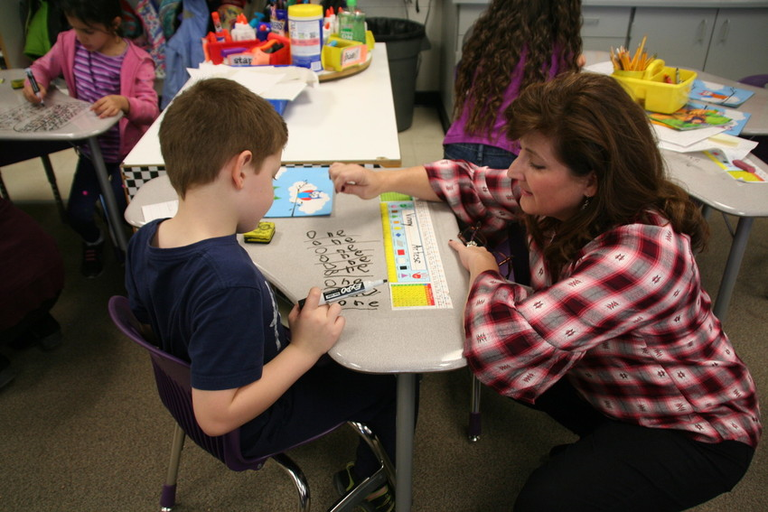 Welchester teacher Kira Jones works with Vinny Artese on trick words in her first-grade classroom in September. Class sizes at Welchester are only slightly higher than before, with the smallest having 18 students in it and the largest with 25 students.