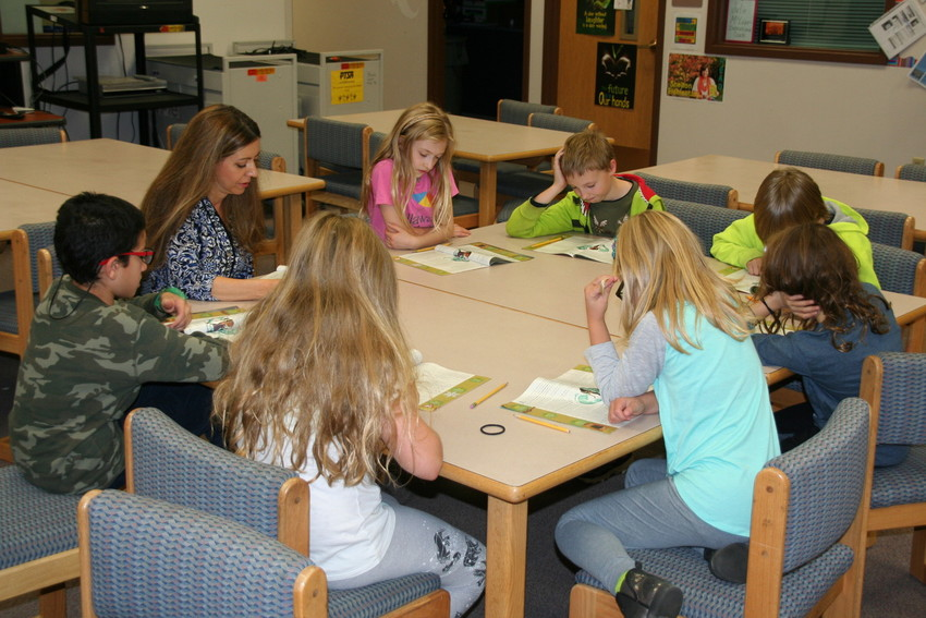 Deborah South, a parent volunteer at Shelton Elementary School, works with a small reading group of fourth graders in the school's library. This year, Shelton got about 100 new students, and about 75 of them came from Pleasant View Elementary School.