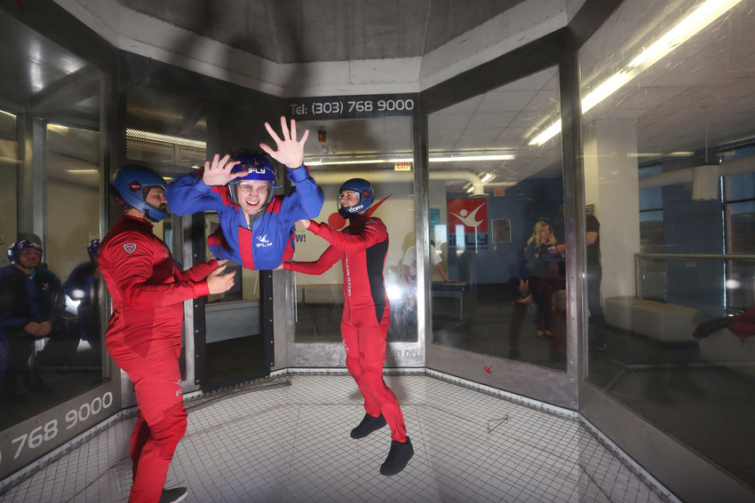 iFLY lead instructor Mike Silva, left, and instructor Cory Pope, right, assist a student from Colorado Center for the Blind at an iSTEM camp on Nov. 13 at the indoor skydiving facility, at 9230 Park Meadows Dr., in Lone Tree.