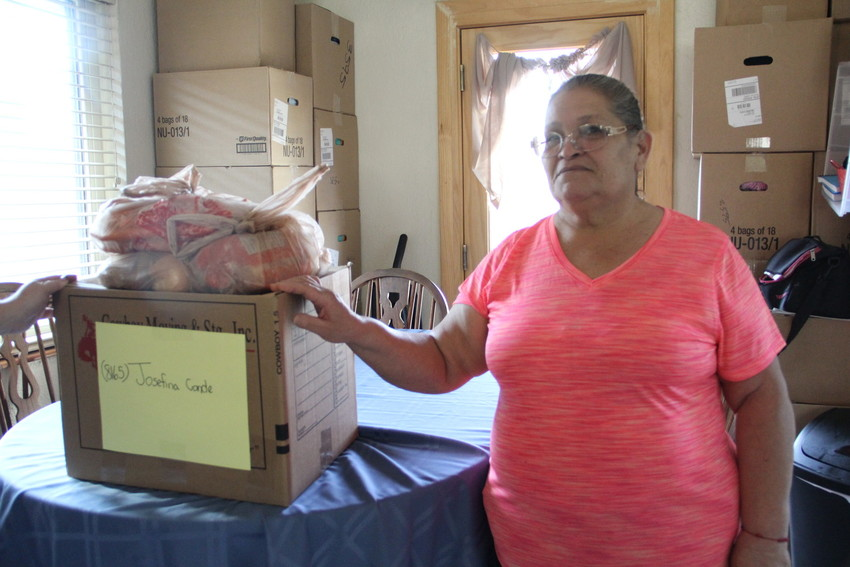 Josefina Conde stands with delivered Thanksgiving food from a volunteer effort at Integrated Family Community Services Nov. 15. Conde lives in Englewood.