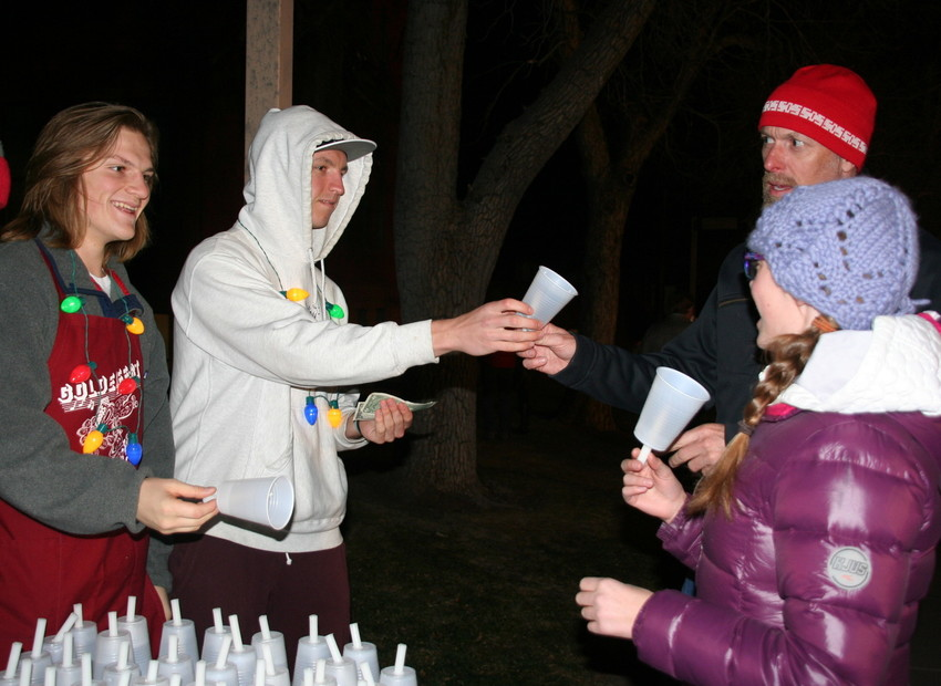 Colorado School of Mines students Dylon Becker, left, and Devan Payne sell Golden residents Chris McGee and his daughter Ella, 13, candles before the two head down Washington Avenue for the 30th annual Candlelight Walk on Dec. 1.