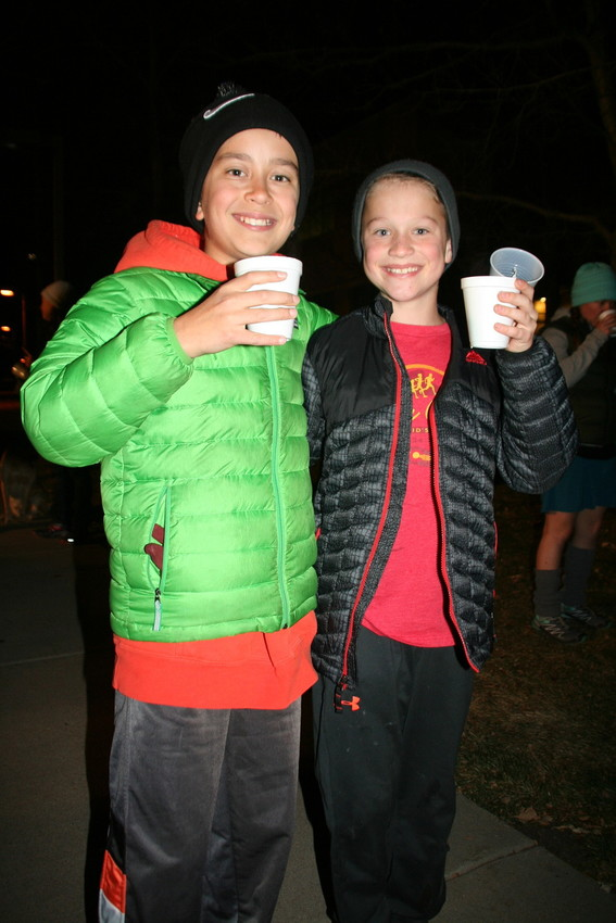 Golden's Torrey Weiner, 11, and Gunnar Tande, 11, ask to get their picture taken with the full cups of hot cider and candles they purchased prior to the walk down Washington Avenue on Dec. 1.