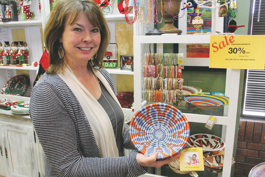 Connie Stevinson, owner of Compleat Lifestyles gift and housewares shop in Centennial, stands in the store holding a traditionally woven Rwandan basket Nov. 28. Stevinson began selling them after meeting members of a women's collective in Rwanda in 2009 that makes them. Photo by Ellis Arnold