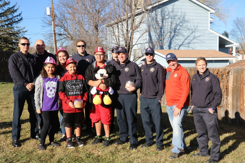 The Balderas-Soto family and Frank Squeo, founder of Baking Memories 4 Kids, and Arvada fire fighters from Arvada Fire Station No. 2. The fire fighters drove Squeo to the Wheat Ridge home of the Balderas-Soto family to present them with a free trip to Florida in March.