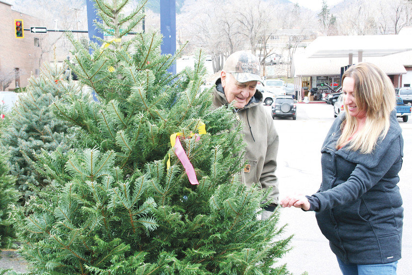 Elmer Dudden, the Golden Optimists' main tree lot organizer, left, assists Allison Sendziak with a tree sale on Nov. 28 at the Optimists' tree lot located on the corner of 19th and Jackson streets in Golden.