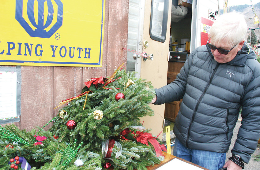 Robb Classens of Golden picks out a wreath from the Golden Optimists to hang on his front door. Local Boy Scouts help run the Optimists' tree lot, and local Girl Scouts decorate the wreaths.