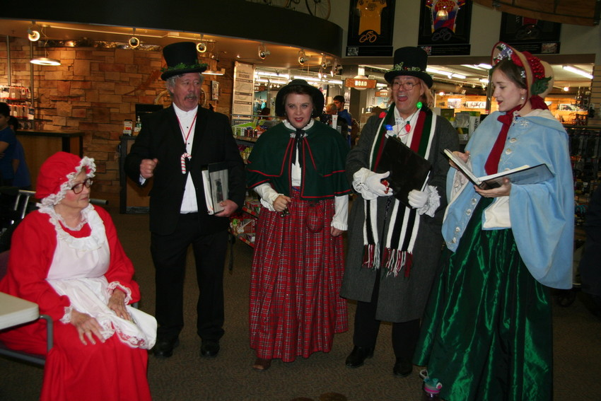 Carolers sing to Mrs. Claus inside the Wheat Ridge Cyclery, where a long line of families awaited a chance to take a photo with Santa.