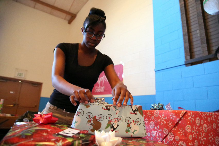 Trinity Williams, a teen mom in the Hope House Colorado residential program, wraps presents for her son, Anthony, after shopping at the organizations Santa Shop.