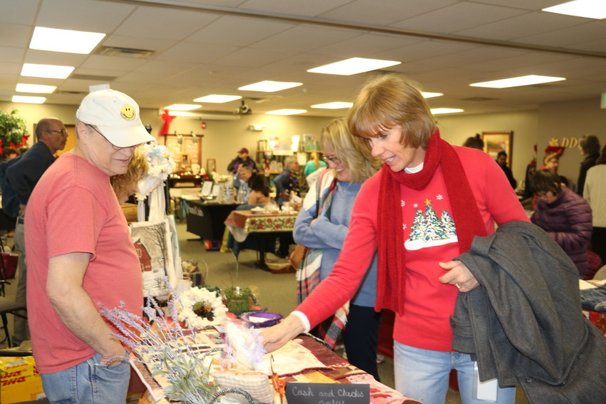 Shoppers examine the wares at the 16th annual Developmental Disabilities Resource Center holiday market on Dec. 7. The annual public event gives shoppers the chance to buy gifts and treats made by clients of the center. There also is live music, and Santa even stops by to visit with shoppers.