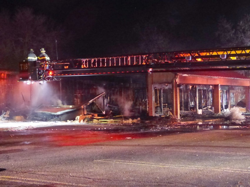Firefighters extinguish hot spots in a burned storefront at the Columbine Square Shopping Center on Jan. 3.