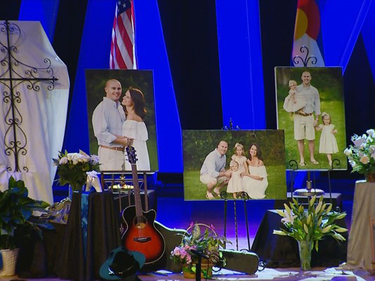 Photos of fallen Douglas County Deputy Zackari Parrish, along with pieces of his past, like his guitar, sit on the stage of Cherry Hills Community Church, 3900 Grace Blvd., for the funeral service on Jan. 5. Image courtesy of 9News