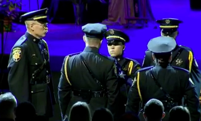 Law enforcement officers lead a military-style honor to close the funeral of fallen Douglas County Deputy Zackari Parrish. The service was held at Cherry Hills Community Church in Highlands Ranch on Jan. 5.  Image courtesy of 9News
