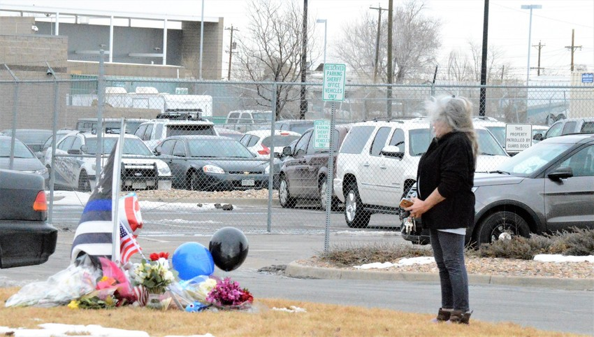 An unidentified woman leaves flowers at an impromptu memorial for Deputy Heath Gumm outside the Adams County Sheriff's Substation at 72nd and Colorado Boulevard Thursday Jan. 25. Gumm was shot in the chest at about 7:30 p.m. Jan. 24 and pronounced dead at a local hospital a short time later,