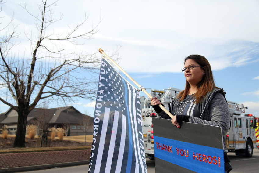 Suzanne Flores, of Aurora, stands alongside the processional for Adams County Deputy Heath Gumm. She attended the event with her mom to show support for the law enforcement community.