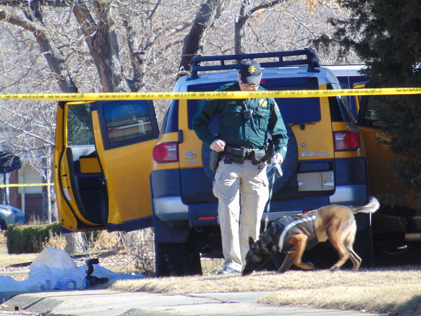 An Arapahoe County Sheriff's Deputy and a K9 unit examine the scene around a car crash on the 500 block of West Caley Avenue on Feb. 6. The driver of the car was found dead from a gunshot wound.