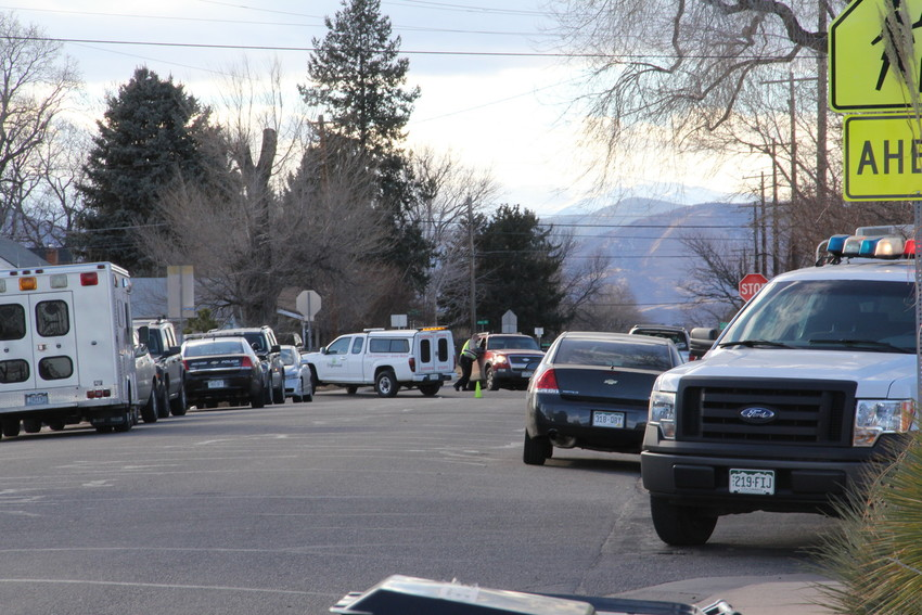 Various law-enforcement vehicles line West Chenango Avenue as police search Colorado's Finest High School of Choice for a possible weapon Feb. 7. Police recovered a gun and took a male student into custody.