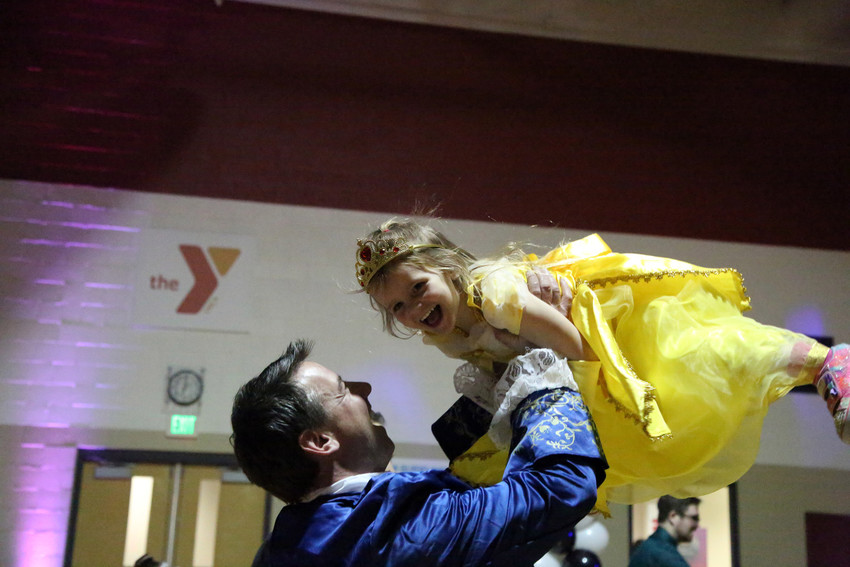 Jay Tracy lifts his daughter, Breckyn, into the air while dancing at the Father, Daughter Princess Ball.