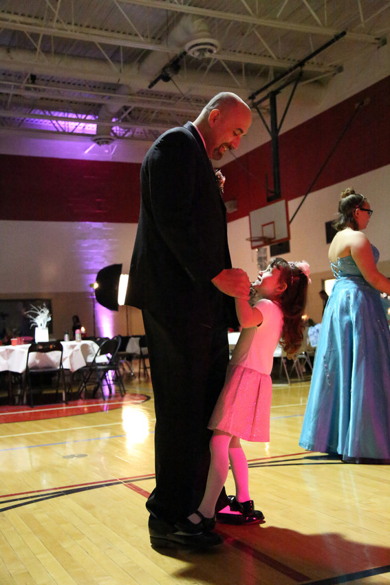 Delaney Smock stands on the feet of her father, Bryan, to dance at their first father, daughter dance together.