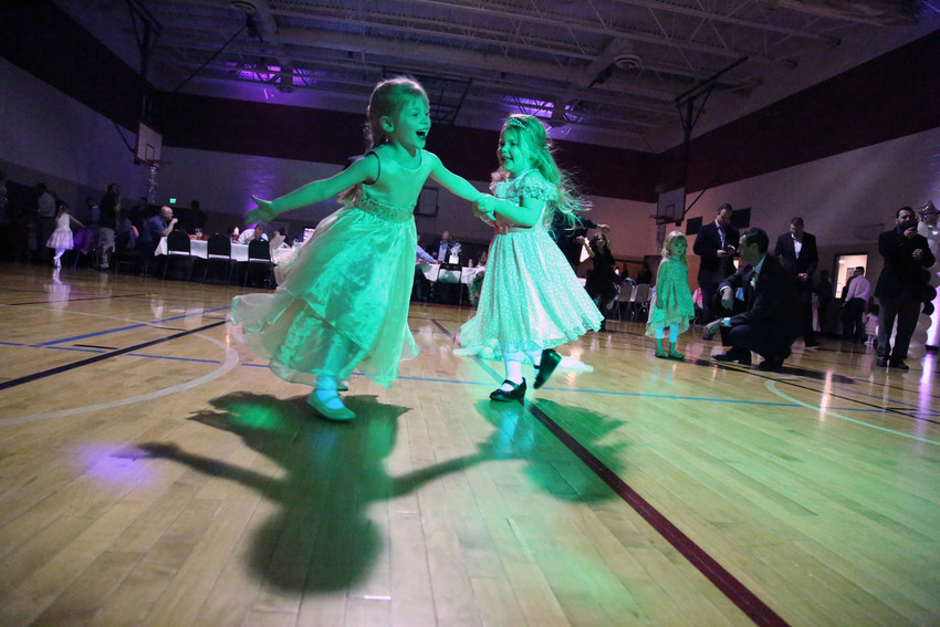 Madilyn Riddle and Caley Edwards spin eachother around the dance floor at the YMCA father, daughter dance.