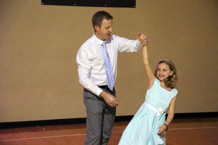 Robert Kaufholz gives his daughter, Evelyn, a spin on the dance floor at the YMCA's father, daughter dance.