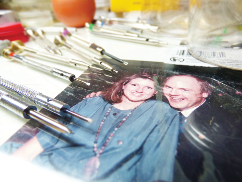 A photo of Karl and Robin Tanke in younger days sits beneath the glass top of the watchmaker's bench. Karl and Robin bought the shop from Karl's dad in 1971.
