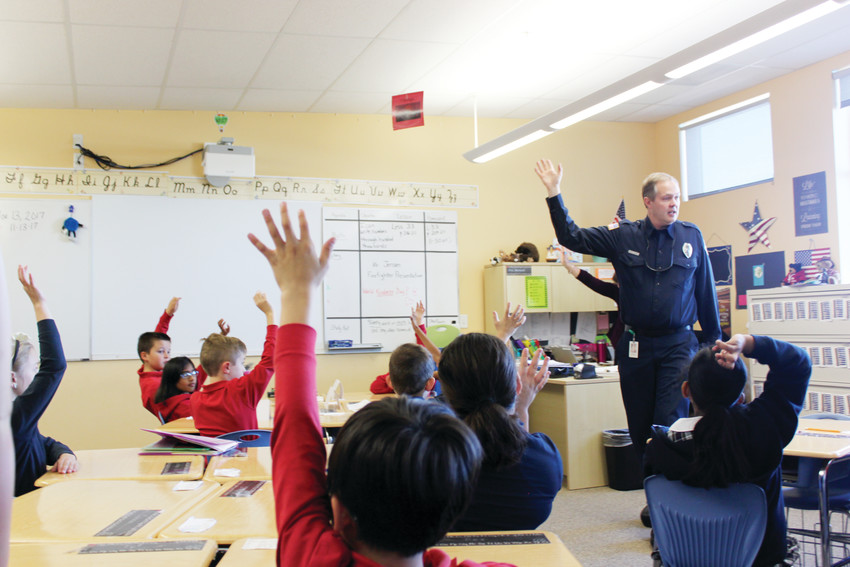 Students at American Academy Motsenbock show by a raise of hands that they know what to do in case of a fire emergency at school, during a home fire safety class taught by Einar Jensen, Risk Reduction Specialist with SMFR.