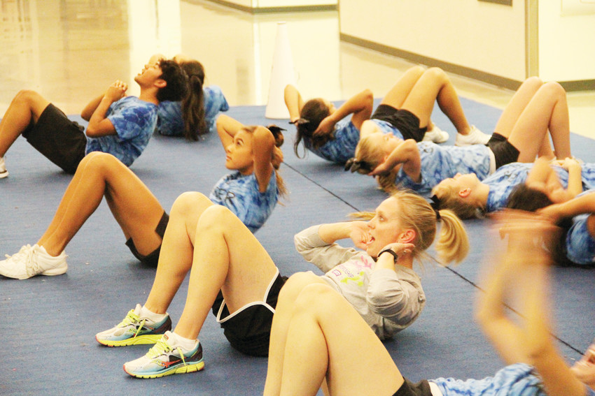 The Englewood High School cheer team does crunches at the end of practice Nov. 17, with coach Ginger Rode, in gray, participating. Rode won the Coach of the Year award in the Colorado 7 League.