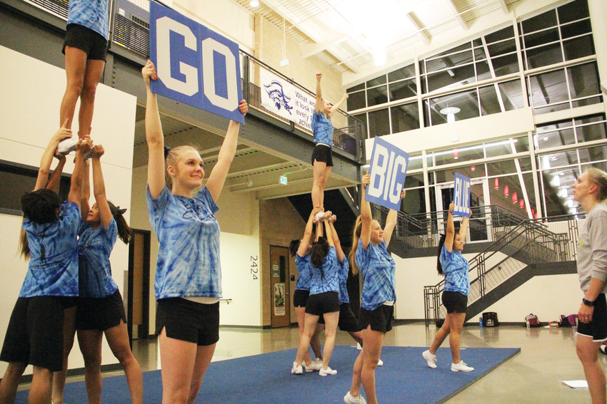 "The Englewood High School cheer team practices at EHS Nov. 17 with signs that spell out, ""Go big blue."" The team, led by coach Ginger Rode, right, won first place at the Colorado 7 League meet in November."