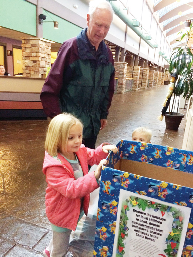 John Ellis helps his grandchildren Chloe Ellis and August Ellis place their bag of toys into a donation box for the Santa House.