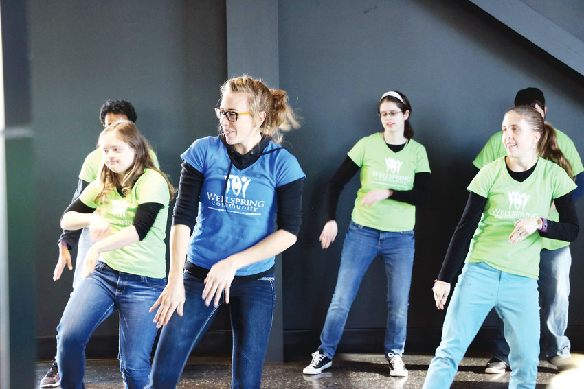 Sarah Deakin, creative arts manager of Wellspring Community, a nonprofit in Castle Rock that provides work, enrichment and educational opportunities for adults with special needs, leads a dance performance at the first-ever Douglas County Gives rally at Schomp MINI on Nov. 29.