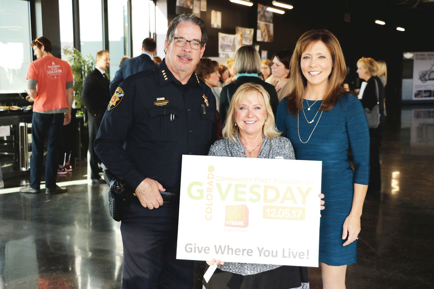 "Douglas County Sheriff Tony Spurlock, left, Douglas County Community Foundation chair Donna Scott and FOX31/Channel 2 Denver anchor Deborah Takahara promote Colorado Gives Day at a Douglas County Gives rally at Schomp MINI in Highlands Ranch on Nov. 29. The statewide day is held on Dec. 5 to encourage the public to donate to nonprofit organizations. ""Give where you live,"" Scott said."