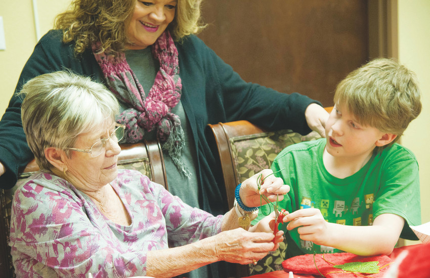 "Judy Roush, left, works on a stocking with Levi, 12, at Highline Place while Shiloh House community liaison Kathy McShane looks on. ""I love when the kids visit,"" Roush said. ""Normally it's pretty boring around here, but I get to see them smile and we get to be busy together."""