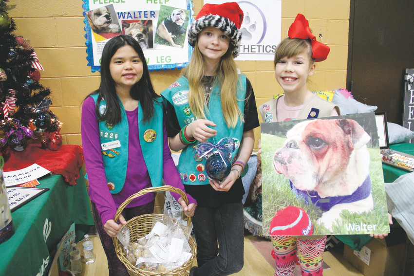From left: Julianna Porter, Diana Baker and Lauren Smith — Girl Scouts from Troop 59 in Lone Tree — stand at a booth to sell self-made crafts, pet beds and dog treats to raise money for a 3D-printed prosthetic leg for a dog in Connecticut on Dec. 2 at the Goodson Recreation Center in Centennial. The proceeds go to Pawsthetics, a nonprofit effort of The 3D Printing Store — one location of which sits at the Centennial Airport — to make prosthetic aids for animals around the United States and beyond.