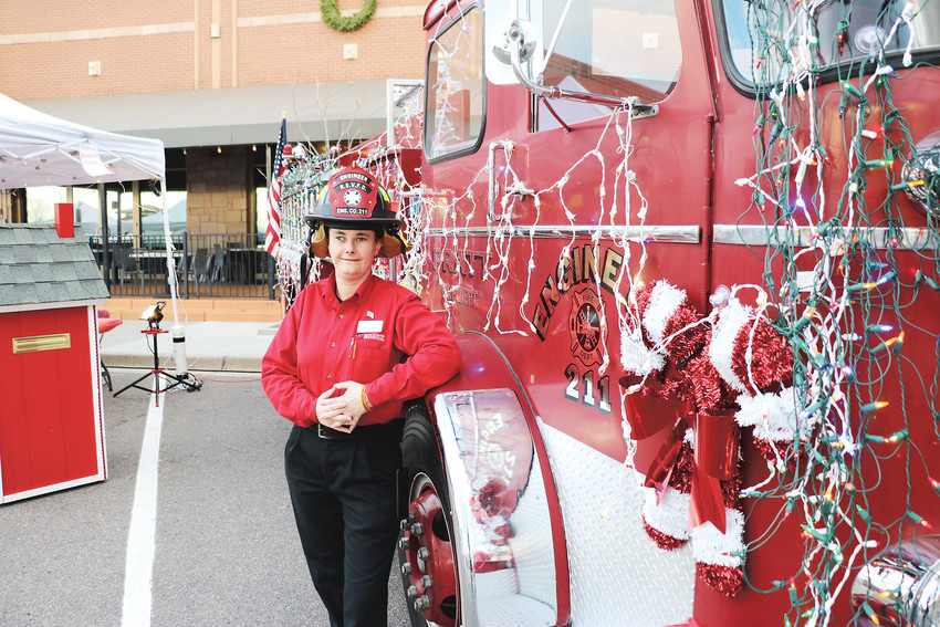 "Ali Guida, a service representative at Schomp, stands next to her ""bouncing baby Betty,"" a fire truck she acquired one year ago, at the annual Hometown Holiday presented by Highlands Ranch Community Association. The fire truck was decked out for the holiday season."