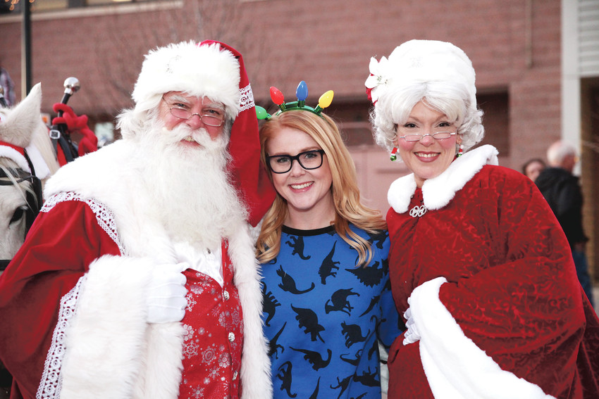 Amanda Arnce, community events manager at the Highlands Ranch Community Association, stands between Mr. and Mrs. Claus at Hometown Holiday at Town Center. The Dec. 1 event included photos with Santa, treats, rides, vendors and more.