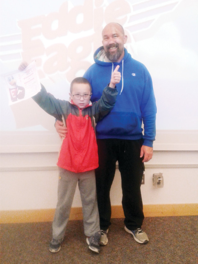 Victor Woelfel, 8, shows off his Eddie Eagle completion certificate with his father, Jason.