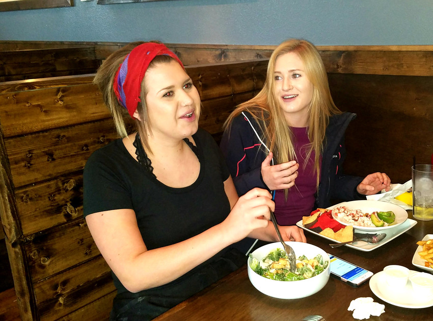 Brianna Mendoza, left, takes a break from serving at The Office Co. to eat lunch with her cousin, Kaycee Daniels.